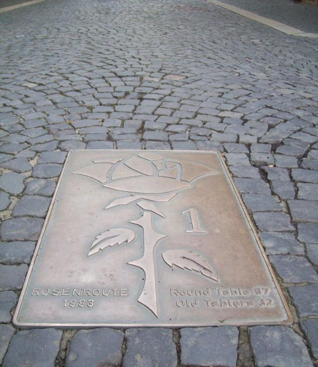 Табличка на мостовой напоминает о 1000 –летней легенде о розовом кусте в древнем г. Хильдесхайме.